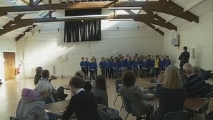 Pupils sing to a crowd in the hall