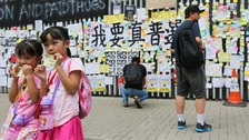 Girls pose for a photo in Hong Kong's Admiralty district