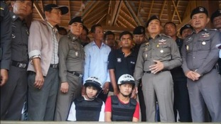 The accused men pose with Thai police