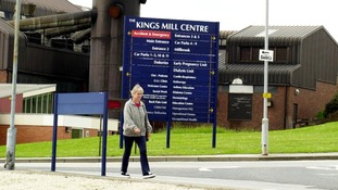 A woman walking past a sign at King's Mill Hospital.