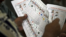 An official counts ballots for the presidential election after the polls were closed in Alexandria