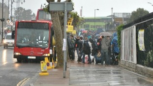 Music fans cue for the bus to get to the Isle of Wight Festival this morning.
