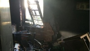 A woman was rescued from her bedroom after a fire in the lounge.