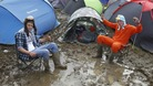Blaise Franklin (left) and Nathan Mursall wallow in the mud at the campsite at the Isle of Wight Festival.