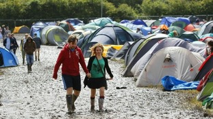 Festivalgoers trudge through the mud in Newport.