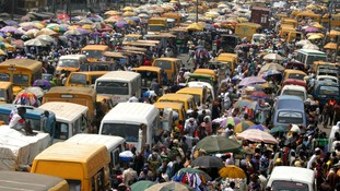 Commuters and traders crowd at a market in Nigeria's largest city Lagos