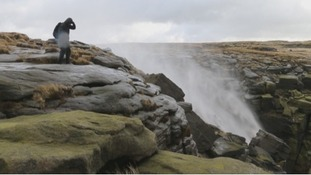 An onlooker watches as the waterfall is blown onto the rocks above.
