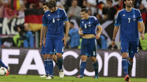 Greek players look despondent after conceding a goal.