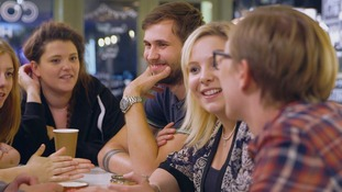 People round a table smiling