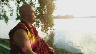 monk looking at a lake