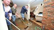 (Left - right) Charlie Openshaw, Colin Rockley and Gary Cooper clear flood water from a house in Croston, Lancashire.