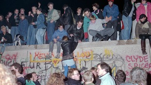 People celebrate the fall of the Berlin Wall at Brandenburg Gate in November 1989