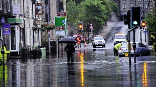 Floodwaters surround local shops today in the centre of Hebden Bridge, West Yorkshire.