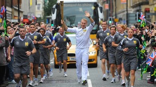 Sir Chris Hoy carrying the Olympic Flame on the Torch Relay leg between Higher Broughton and Manchester.