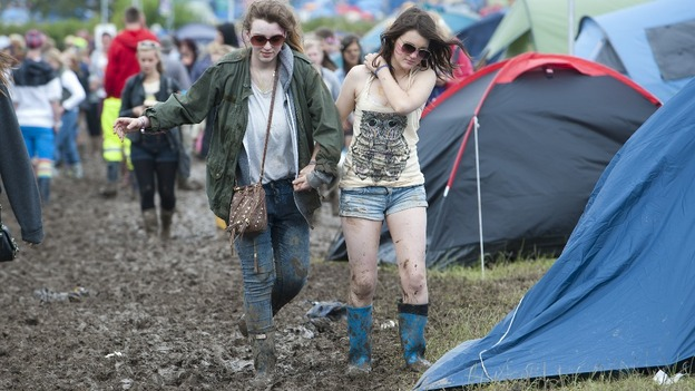 Campers brave the mud during wet weather at the Isle of Wight festival.