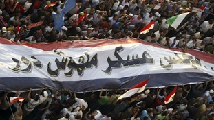 Supporters of the Muslim Brotherhood's presidential candidate Mohamed Morsi surround a giant banner