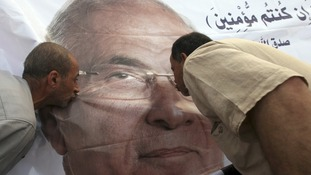 Supporters of former prime minister and presidential candidate Ahmed Shafik kiss his poster during a protest