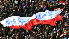 Egyptian protesters march with a huge flag during a rally at Tahrir Square in November 2011