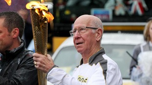 ir Bobby Charlton holding the Olympic Flame on the Torch Relay leg between Salford and Moss Side.