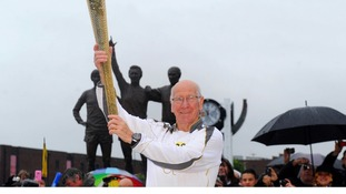 Sir Bobby Charlton holding the Olympic Flame outside Old Trafford football stadium