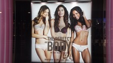 The advertisement shows three women wearing Victoria's Secret lingerie