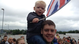 Boy on man's back with flag