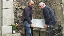 Stonemasons adding names to Diss war memorial.