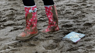 Festival reveller wades through the mud in wellies