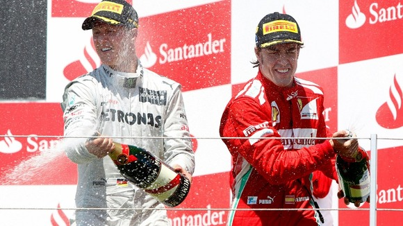 Ferrari Formula One driver Fernando Alonso, from Spain, right, celebrates his victory next to Mercedes driver Michael Schumacher, left.
