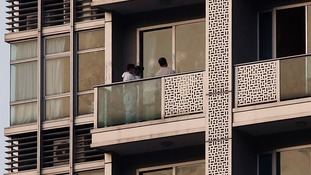 A policeman takes a photo on the balcony of a unit in which two women's bodies were found in a flat at Hong Kong's Wanchai district.