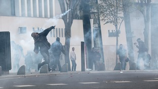 A protestor throws a tear gas canister during clashes with police on the sidelines of a demonstration against police violence in Nantes.
