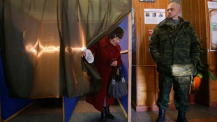 A woman leaves a voting booth during the self-proclaimed Donetsk People's Republic leadership
