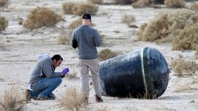 Investigators inspect wreckage from the crash of Virgin Galactic's SpaceShipTwo near Cantil, California