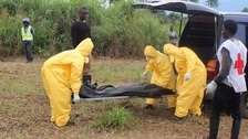Health workers remove the body of an Ebola victim.