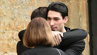 Michael Bellingham, son of the late Lynda Bellingham, is hugged as he arrives for the funeral of his mother at St Bartholomew's Church