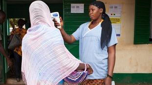 Mali healthworker checks a woman's temperature