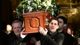 Michael Pattemore carries his wife Lynda Bellingham's coffin with sons Robert and Michael after her funeral service.