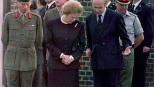 Margaret Thatcher looks at floral tributes after the bombing
