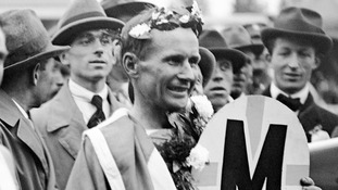 Hannes Kolehmainen of Finland draped in the Finnish flag and crowned with a wreath of laurels after winning the Marathon in 1920
