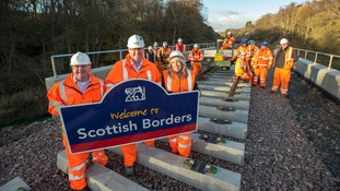 Scottish Borders Council Leader, Councillor David Parker, Network Rail project manager for the central and south sections of the Borders Railway, Ken MacGillivray and Scottish Borders Council Chief Executive, Tracey Logan, join the Borders Railway rail installation team as the rails cross into the Scottish Borders at Cakemuir Burn.