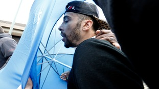 Dappy arrived in court shielded by a blue umbrella.