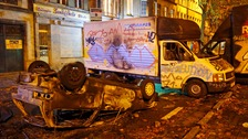 A burnt-out and overturned vehicle is seen after clashes between demonstrators and riot police in central Brussels.
