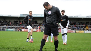 Referee Tim Robinson checks the pitch