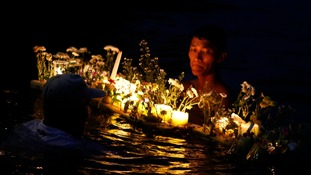 Typhoon survivors bring lighted candles and flowers to the sea to commemorate the victims who perished during the onslaught of Typhoon Haiyan a year ago in Tacloban city.