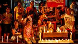 Typhoon survivors light candles along a sidewalk and display a placard to commemorate the victims who perished during the onslaught of Typhoon Haiyan