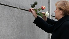 German Chancellor Angela Merkel places a rose at the Berlin Wall memorial in Bernauer Strasse.
