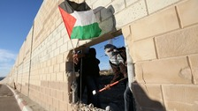 Palestinian activists break down the separation wall