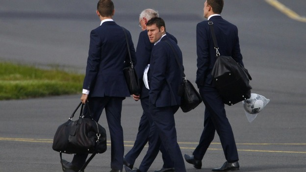 The England players land in the UK after defeat against Italy.