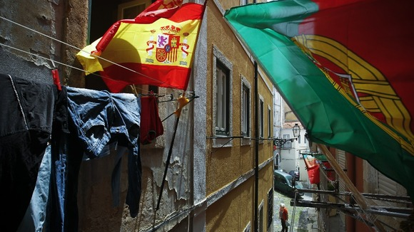 Portugal and Spain's flags wave at the balconies of a narrow street of Lisbon's Mouraria neighborhood.