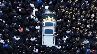 Mourners gather around the remains of Aryeh Kopinsky in Jerusalem earlier today.